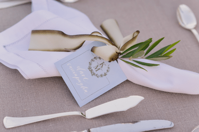 An Elegant White Linen Napkins With Ribbon And An Olive Sprig Image Provided By White Lilac Event Design