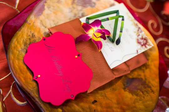 Add a special touch to table assignments with a rush formed into a geometric shape and accompanied by a lovely orchid. Design by Lois Mathews Design Photography by Kristina Chartier Photography