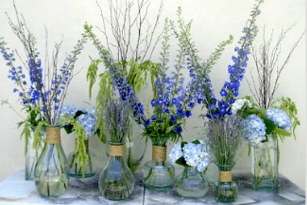 A collection of small vases wrapped with jute and filled with branches, hydrangeas, larkspur and lavender create a woodsy feeling. Image provided by Flowers Forever Florist