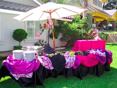 Bright fabric draped tables make an attractive set up for a buffet. Image provided by Gourmet Gourmet Catering