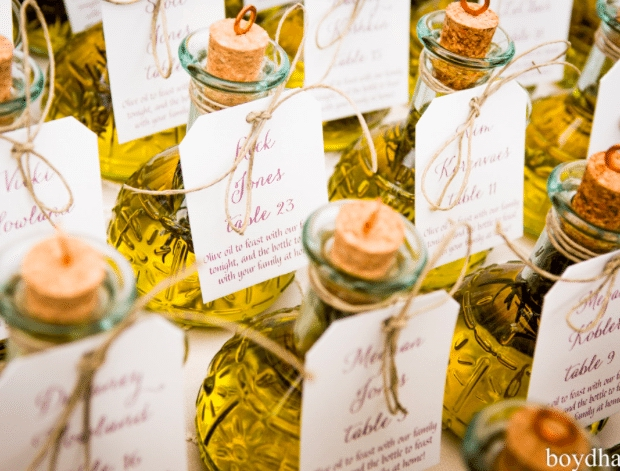Bottles of olive oil make a bright display and fun take home gift, while directing guests to their seats. Image provided by Everafter Event Design. Photography by Boyd Harris Photography Make certain each guest receives a thank you gift by attaching their table assignment to it. Image provided by Hulse PhotographyMake certain each guest receives a thank you gift by attaching their table assignment to it. Image provided by Hulse Photography. PLATINUM LOCATIONS PLATINUM LOCATIONS EVENT DESIGNERS
