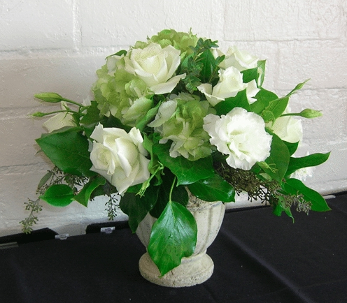 The classic look of white roses and rich, green foliage in a classic footed, white vase. Image provided by Petal People