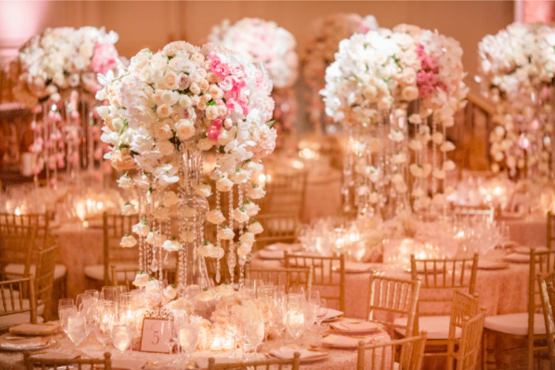 Orchids and roses are softly lit by abundant candles. Image provided by Whit Lilac Event Design Photography by Kristi Klemens Photography