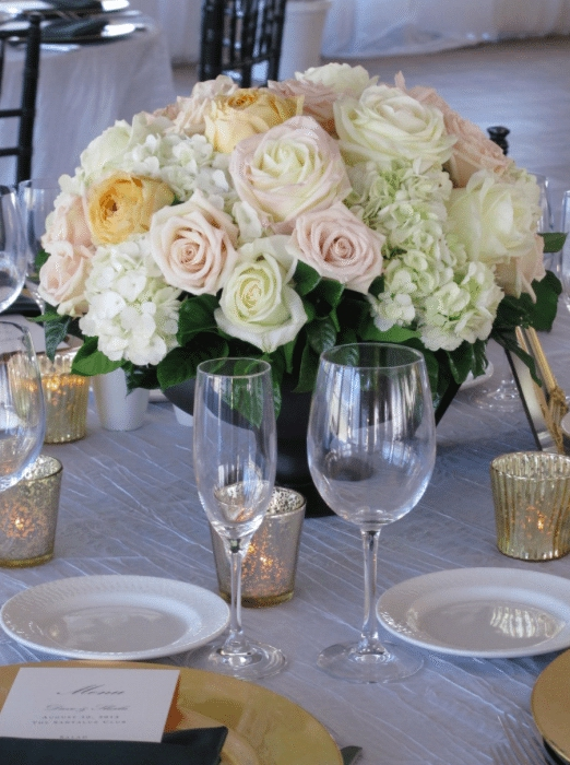 The soft colors of lacy petals are highlighted by low candles. Image provided by Organic Elements