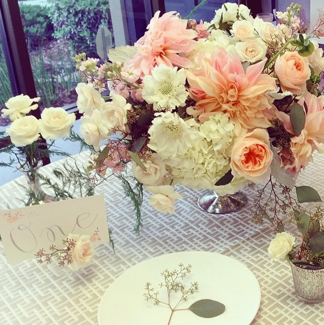 A mix of dahlias, roses, hydrangeas and touches of eucalyptus on a subtly patterned cloth create a dreamy tablescape. Image provided by Organic Elements