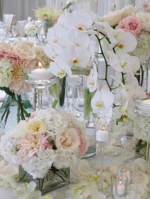 Classic white orchids, cream and pink roses in low arrangements invite guests to enjoy the scent and beauty of the flowers. Image provided by Organic Elements